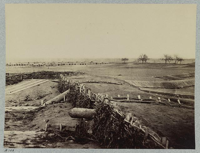 Confederate fortifications at Centreville, Va. March 1862. Quaker guns in foreground. Winter barracks in background.