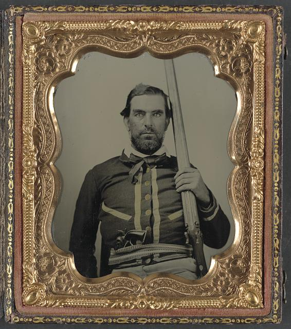 [Unidentified soldier in Confederate quantrillian battleshirt with double barrel percussion shotgun and cocked Colt Navy revolver]