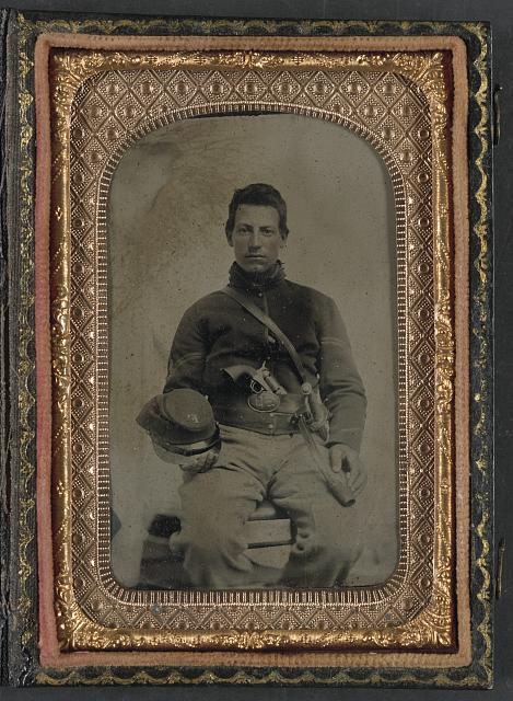 [Unidentified soldier in Union uniform with Company F hat and upside down U.S. belt buckle, armed with Colt revolver and cavalry sword]