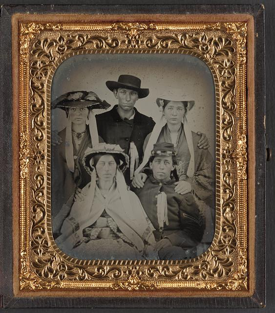 [Unidentified soldier in Union uniform with three unidentified women in bonnets and one unidentified man]