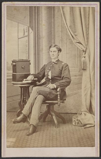 [Unidentified soldier in uniform with cabinet stereograph viewer]