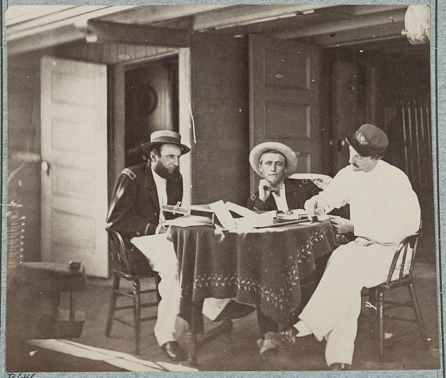 [Three soldiers seated around a table]