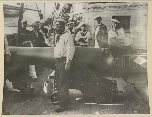 [Boatswain piping in front of large cannon on deck of U.S. Naval warship; other sailors standing in background]