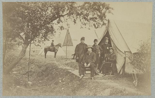[Group of five officers outside a tent with a man sitting on a horse in the background]