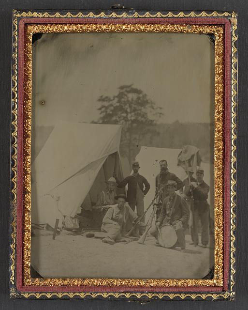 [Seven unidentified soldiers in Union uniforms with drum and stacked rifles in front of tent]
