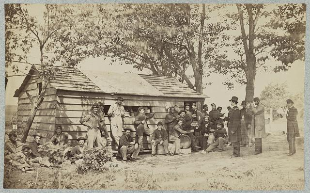[Group of officers and soldiers outside a sutler's store]