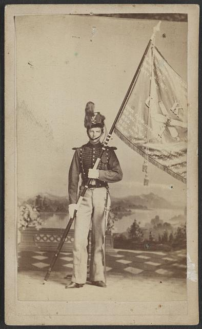 [Unidentified soldier in artillery uniform and Shako hat with Battery K, 1st U.S. Artillery flag and battle honors in front of painted backdrop showing garden leading to river]