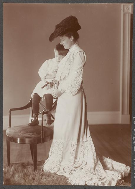 [Edith Kermit Carow Roosevelt, full-length portrait, standing, facing left, with arm around young Quentin Roosevelt, who is seated on back of chair]