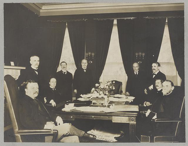 [President Theodore Roosevelt with members of his cabinet seated and standing around a table]