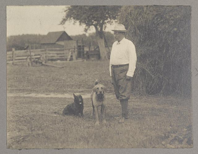 [Theodore Roosevelt standing with two dogs next to haystack]
