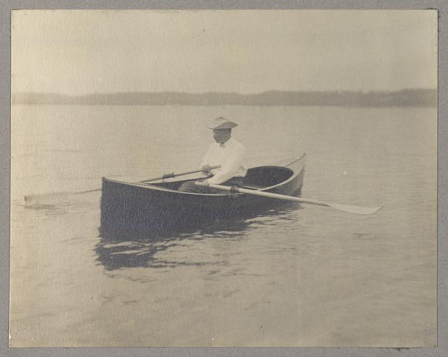 [Theodore Roosevelt, seated in canoe, rowing]