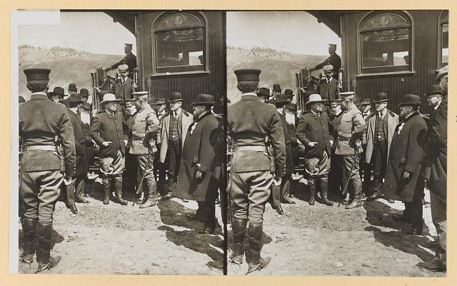 [Theodore Roosevelt standing by a railroad car talking with a group of men]