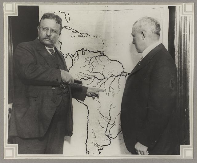 [President Roosevelt pointing at a map of South America towards the area explored during the Roosevelt-Rondon Scientific Expedition in Brazil as another man looks on]