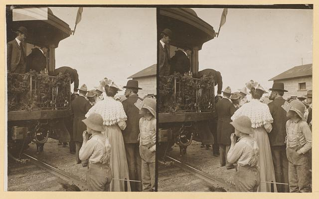 Theodore Roosevelt, leaning over the rear platform of railroad car to shake hands]