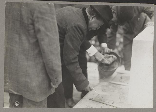 [President Theodore Roosevelt applying mortar with a trowel]
