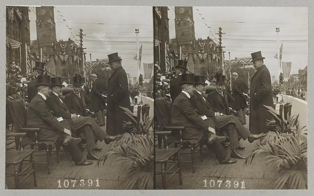 [President Theodore Roosevelt seated talking with men at parade]