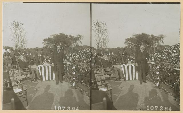 [Theodore Roosevelt leaning against platform railing with the crowd behind him]