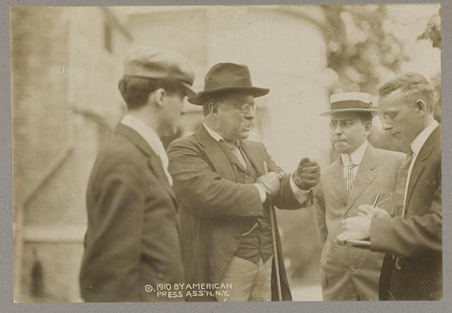 [Theodore Roosevelt speaking with three men, probably reporters]
