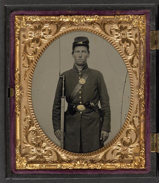 [Isaac Yost of Company C, 118th Regiment Illinois Infantry, standing in uniform with bayoneted musket and revolver]