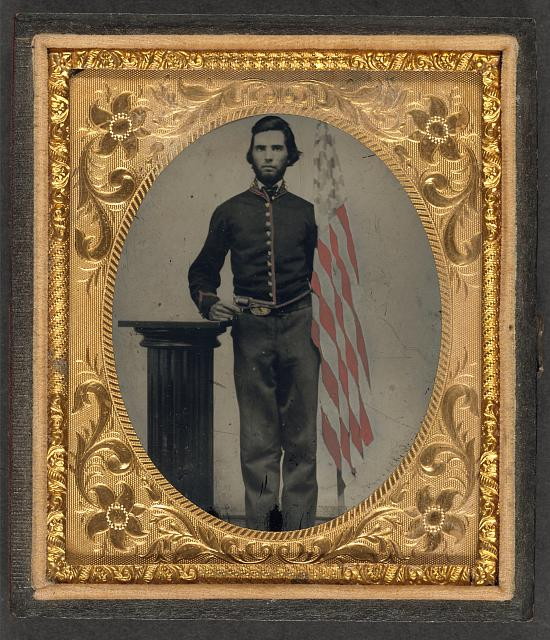 [Unidentified soldier in Union artillery uniform standing next to pedestal holding revolver and American flag]