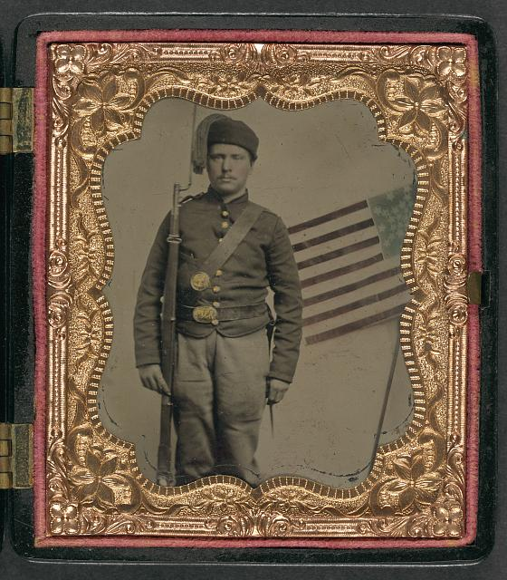 [Unidentified soldier in Union uniform and fez with bayoneted musket in front of painted backdrop showing American flag]