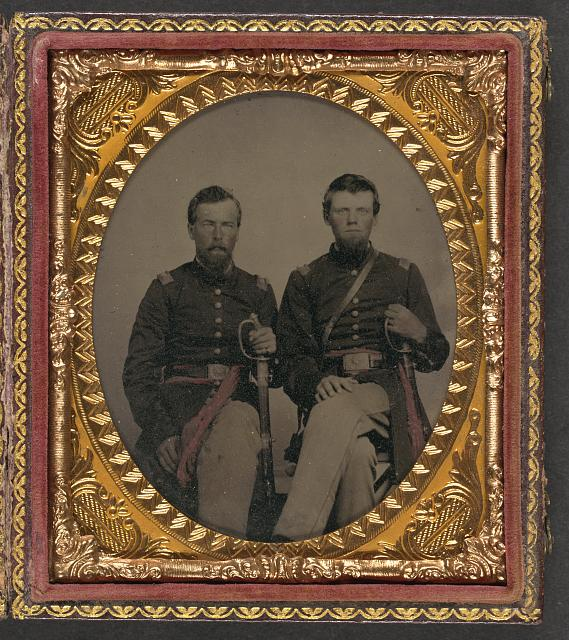 [Two unidentified soldiers in Union captain's uniform and lieutenant's uniform, holding foot officers' swords, wearing frock coats, over-the-shoulder belt for sword attachment, and red sashes]