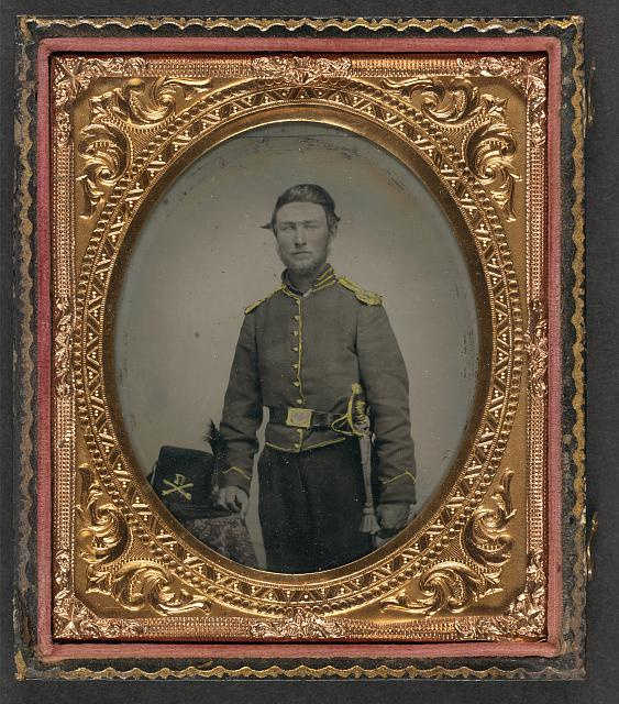 [Unidentified soldier in Union cavalry uniform with cavalry saber next to table with Cavalry Company D Hardee hat]