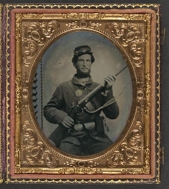 [Unidentified soldier in Union uniform with eagle breast plate, cartridge box, and cap box holding musket with bayonet in scabbard]