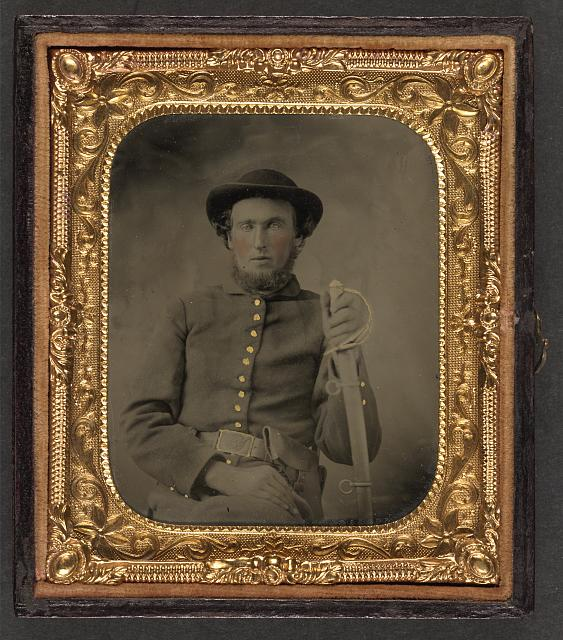 [Unidentified soldier in Union uniform and slouch cap sitting with holstered revolver and cavalry saber]