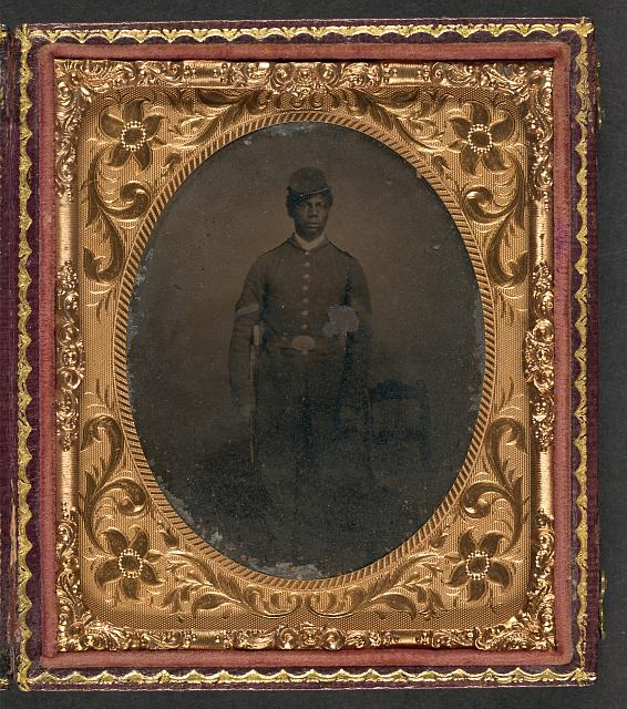 [Unidentified African American soldier in Union uniform standing next to chair with bayonet]