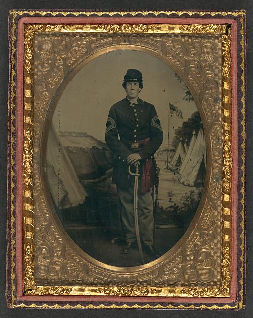 [Unidentified soldier in Union sergeant-major's uniform with sash standing with sword in front of painted backdrop showing military camp]