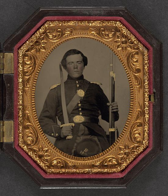 [Unidentified soldier in Union uniform and shoulder scales with musket and sword]