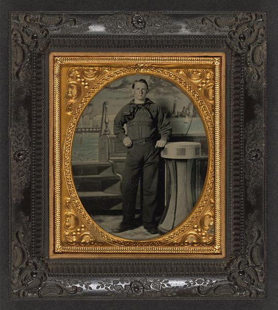 [Unidentified sailor in Union uniform standing in front of painted backdrop showing naval scene]