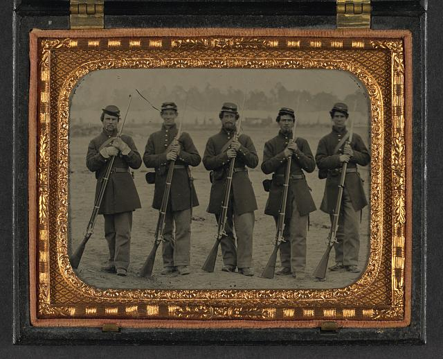 [Five soldiers, four unidentified, in Union uniforms of the 6th Regiment Massachusetts Volunteer Militia outfitted with Enfield muskets in front of encampment]
