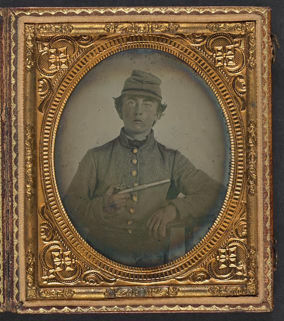 [Unidentified young soldier in Confederate shell jacket and forage cap with single shot pistol]