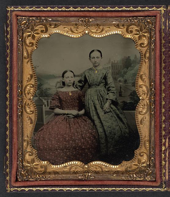 [Two unidentified young women wearing printed dresses and necklaces in front of painted backdrop showing plantation]