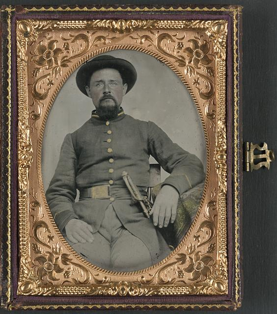[Unidentified soldier in Confederate uniform and derby hat with sword]
