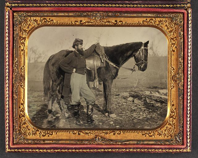[John E. Cummins of the 50th, 99th, and 185th Ohio Infantry regiments in Union uniform next to a horse]