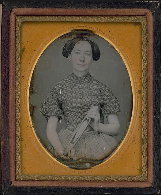 [Maria Boyd holding a weaving shuttle, half-length portrait, facing front]