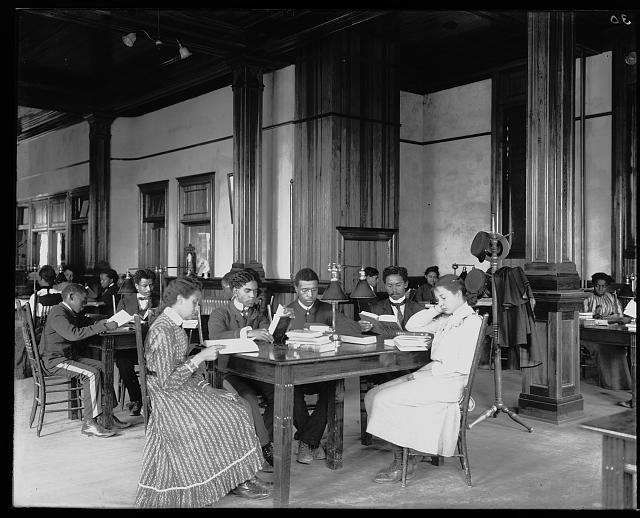 [Interior view of library reading room with male and female students sitting at tables, reading, at the Tuskegee Institute]