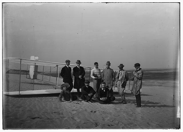 [Group portrait in front of glider at Kill Devil Hill. Sitting: Horace Wright, Orville Wright, and Alexander Ogilvie; standing: Lorin Wright, and group of journalists, including Van Ness Harwood of the New York World, Berges of the American News Service, Arnold Kruckman of the New York American, Mitchell of the New York Herald, and John Mitchell of the Associated Press; Kitty Hawk, North Carolina]