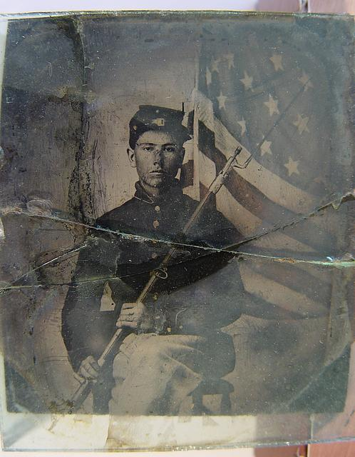 [Unidentified soldier in Union uniform with bayoneted musket in front of American flag]