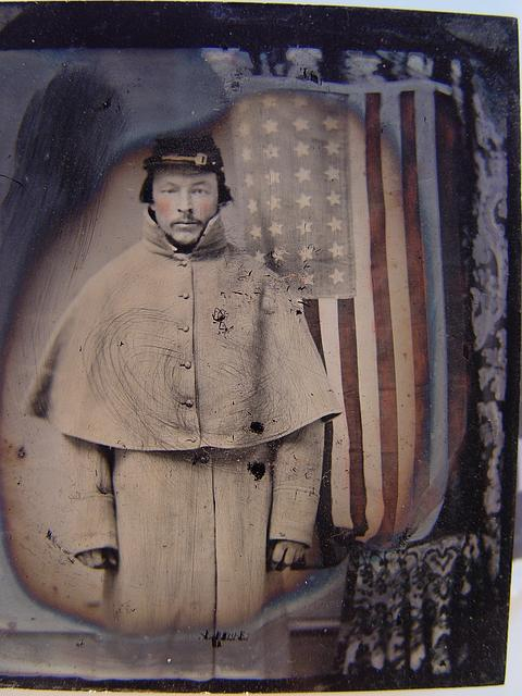 [Unidentified soldier in Union uniform with greatcoat in front of American flag]