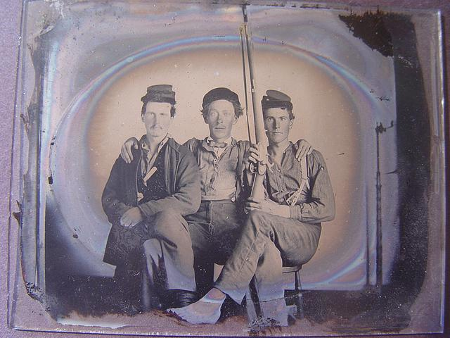 [Three unidentified soldiers in forage caps with musket, probably Union uniforms]
