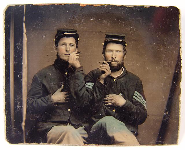 [Two unidentified soldiers in Union uniforms holding cigars in each others' mouths]