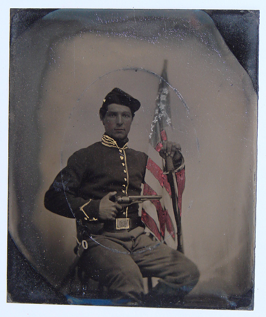 [Unidentified soldier in Union uniform with Colt Army Model 1860 revolver, sword, and American flag]