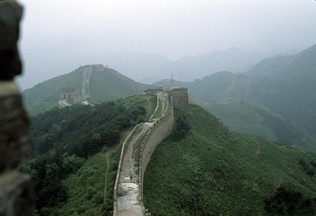 [Bird's-eye view of the Great Wall of China along mountain ridges, disappearing into the haze in the distance]