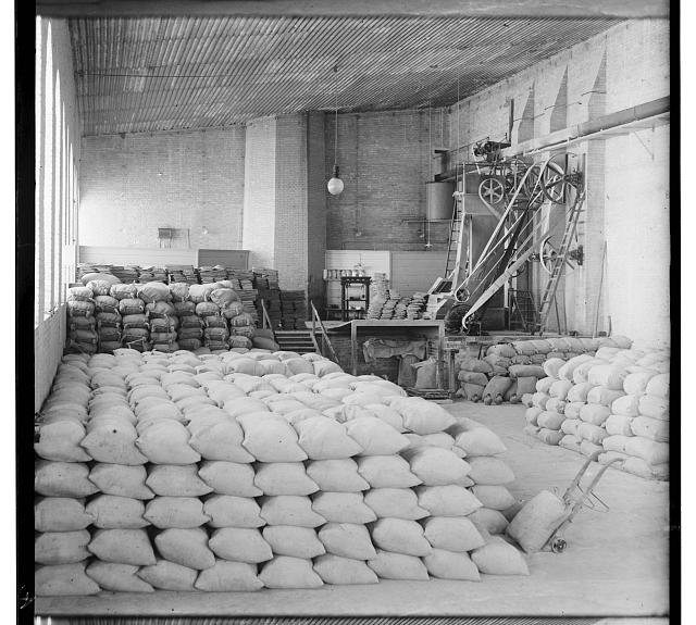 [Sacks stacked in storage room, pulley system machinery mounted along wall]