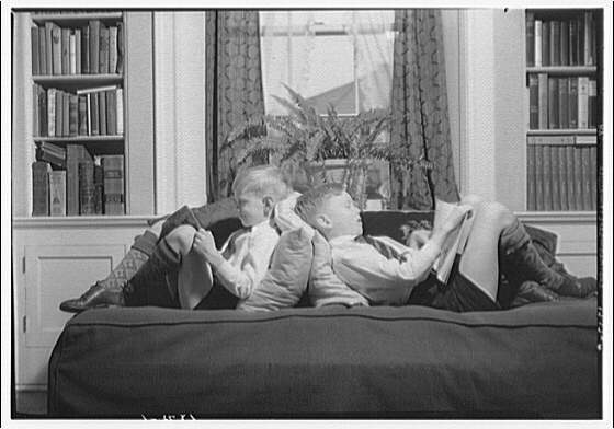 Wyckoff children. Two boys reading on couch VI