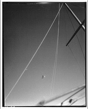 American Clipper. View of American Clipper plane in sky seen beyond boat mast
